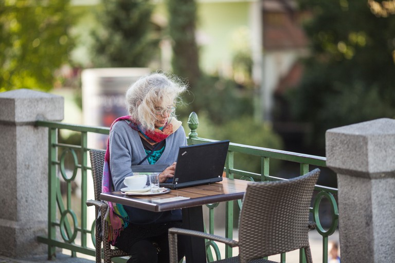 Woman working with laptop outside in Prague
