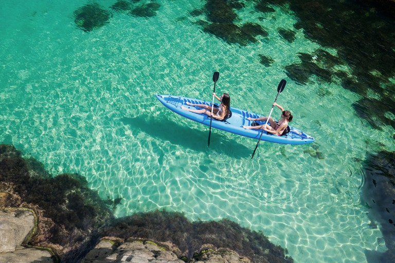 Two women kayaking on while travelling