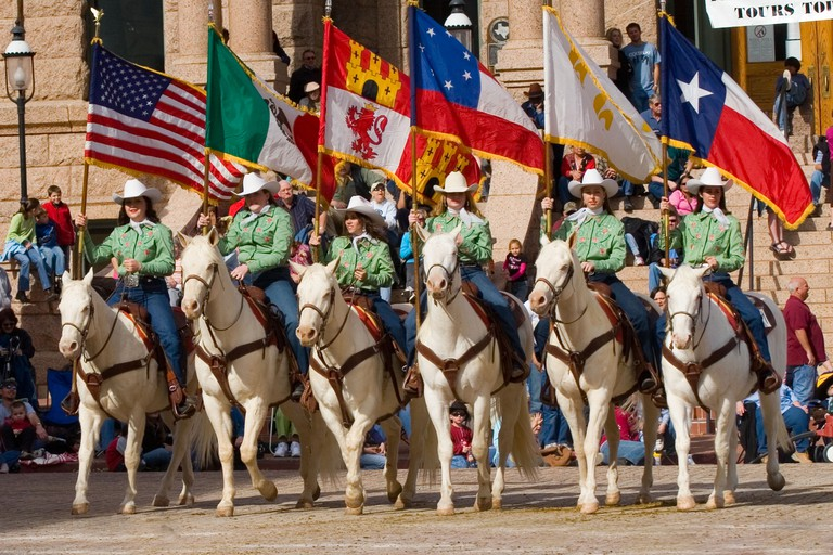 Six Cowgirls on White Horses Carry Flags That Have Flown Over Texas, America, Mexico, Spain, Confederacy, France, and Texas