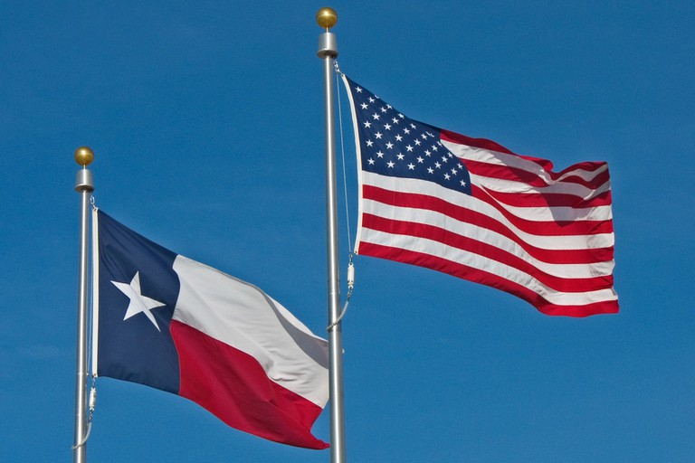 American and Texas Flags flying from flagpoles against a blue sky