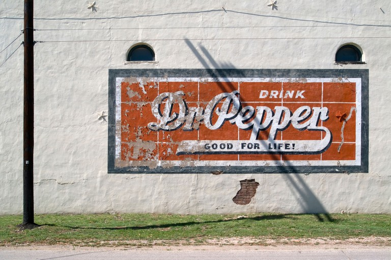 View of a vintage painted Dr Pepper Ad. with door arched window sand telephone pole.