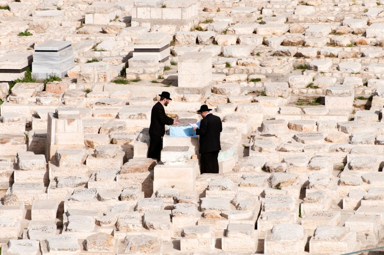 Orthodox Jews prying at one of the tombs in the cemetery on the Mount of Olives Jerusalem, Israel