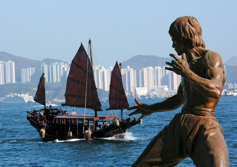 Dukling boat in Victoria Harbour against Bruce Lee statue. Hong Kong.