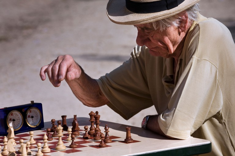 Old retired man playing chess at the Jardins du Luxembourg, Paris