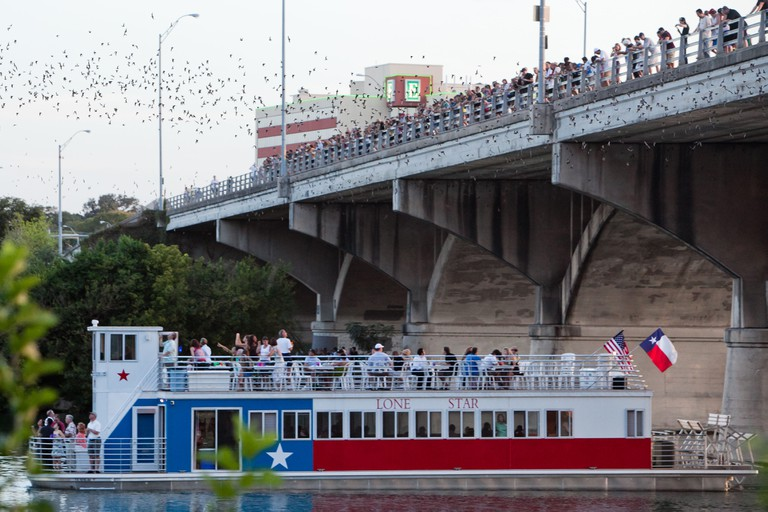 Bats Emerge from the Congress Bridge in Austin, Texas as the Lonestar Riverboat passes underneath