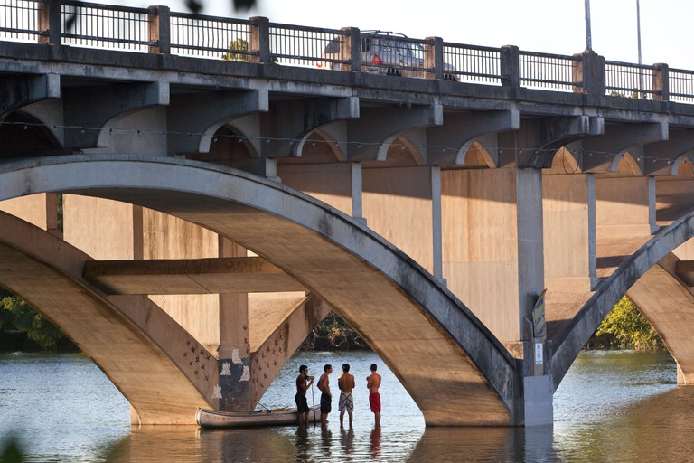 Canoers enjoy the shade underneath the Lamar Bridge