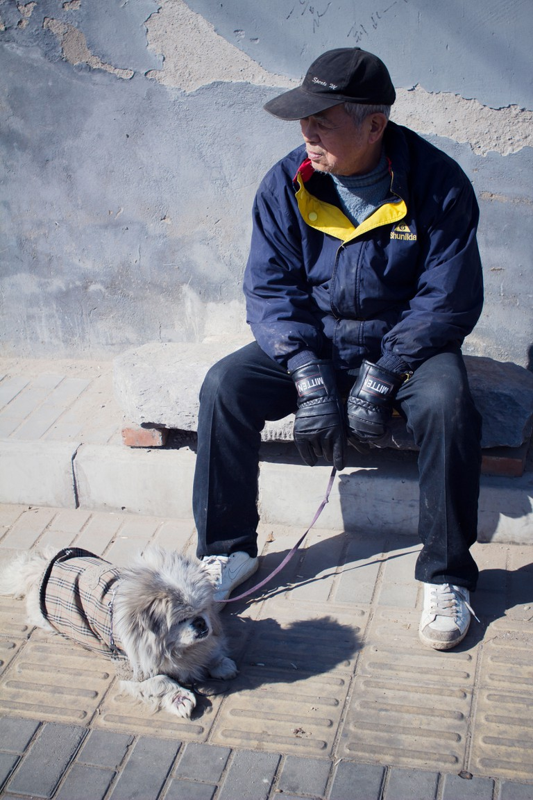 A man sitting with his dog in Beijing.
