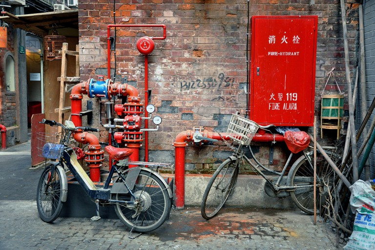 Bikes and red water pipes in an alley of Tianzifang, a renovated area in the French Concession near Taikang Lu, Shanghai - China