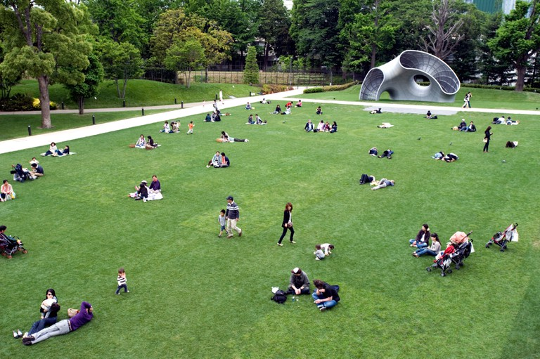 People relaxing on lawn by sculpture at new Tokyo Midtown mixed-use shopping, hotel and residential complex in Roppongi, Tokyo