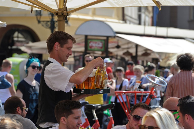 A barman holding a tray of beer, Prague