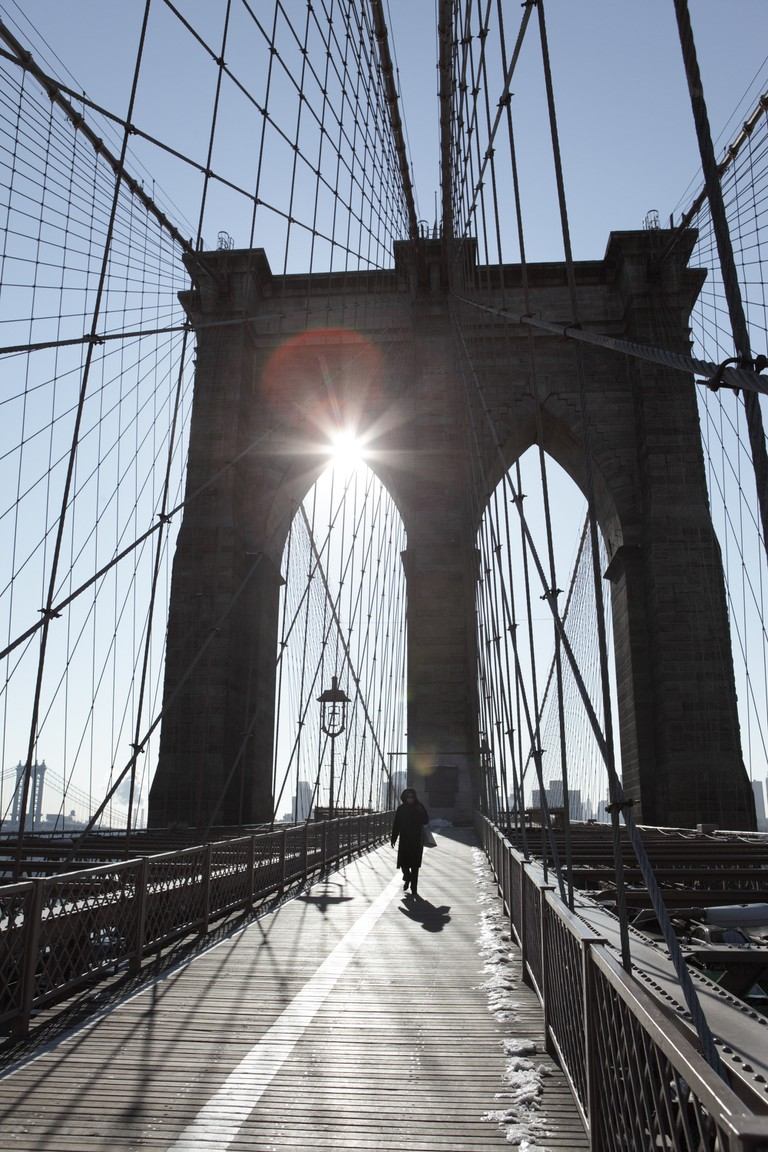 Walking across the Brooklyn Bridge at dawn is the ultimate New York City experience for solo travelers