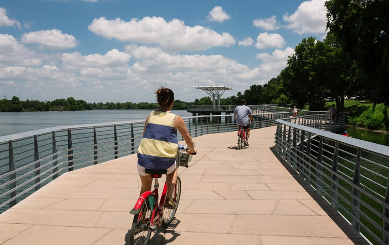 Bicyclists ride on the Austin Boardwalk over Ladybird Lake