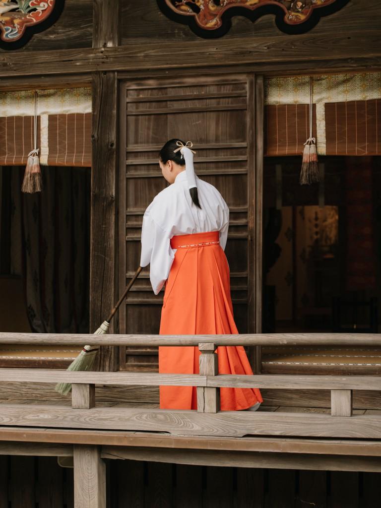 A monk sweeps the porch at Oarai Isosaki Shrine