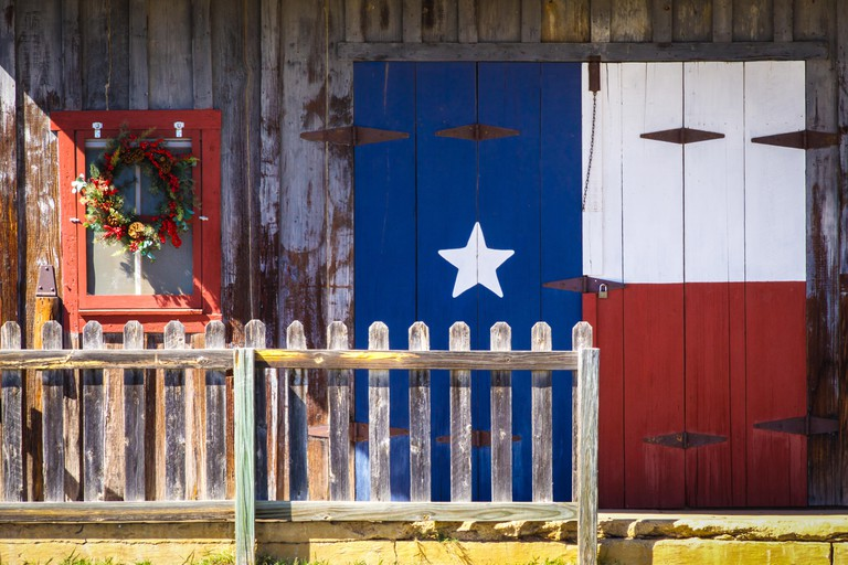 Front porch of old farm building painted in Texas flag, in the Central Texas Hill Country.