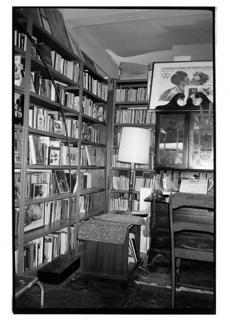 Bookshelves and desk in living room inside Lesbian Herstory Archives.