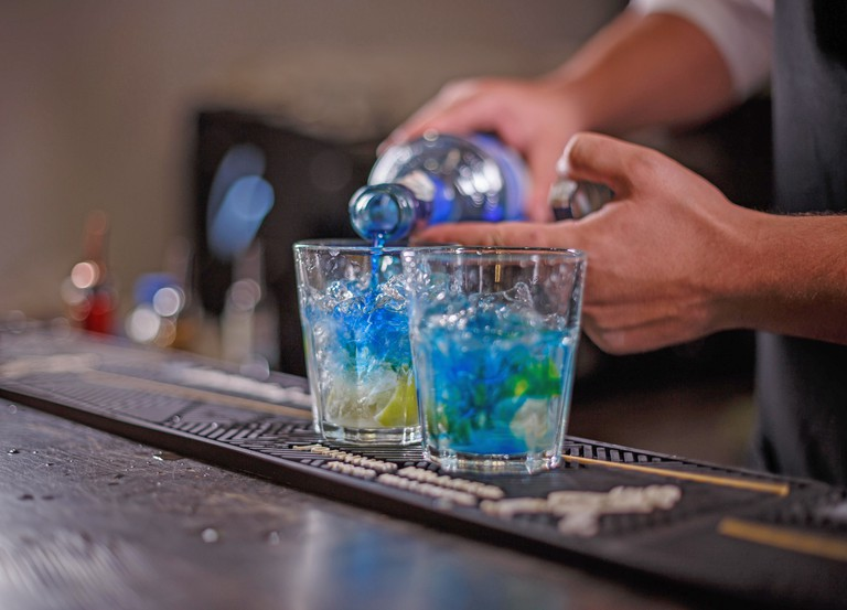 Barman pouring drink into a cocktail glass filled with ice cubes