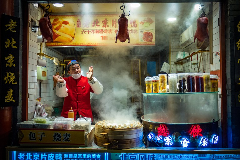 Chinese vendor selling Beijing duck and Baozi at night, China