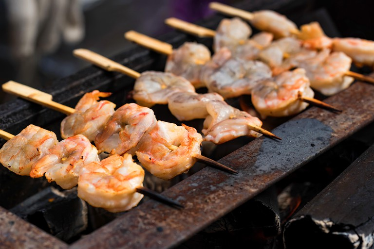 Roast shrimp on skewers on metal grid