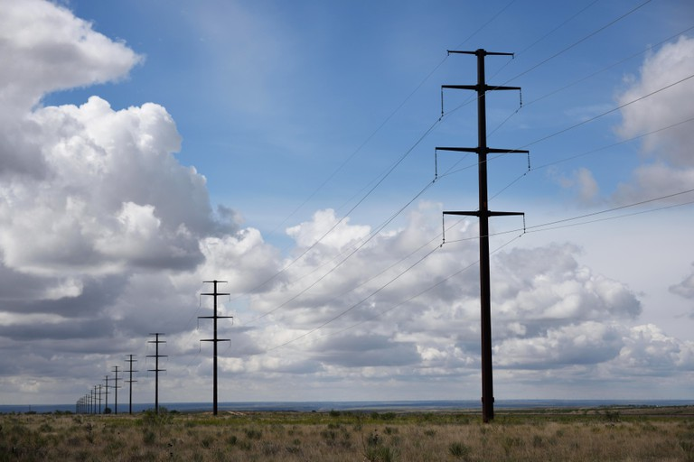 Row electricity poles and and high voltage power lines and rural landscape with blue sky and clouds near Amarillo, Texas, USA.