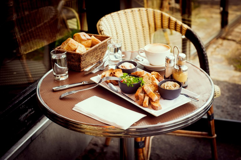 French breakfast for two in a Parisian street cafe - baguette, guacamole and salmon rillettes.