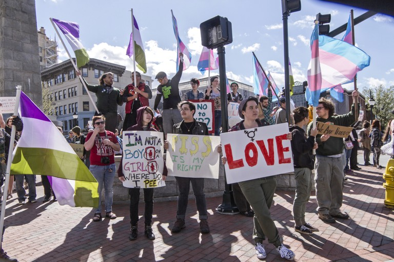 LGBT protest rally against the HB2 Law in North Carolina with symbolic flags, transgender symbols and signs about bathroom restrictions, pride, and love.