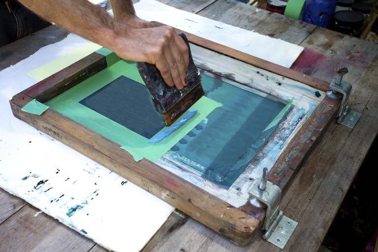 A man in the process of creating a print