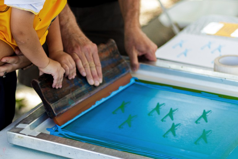 Small boy being shown how to screen print