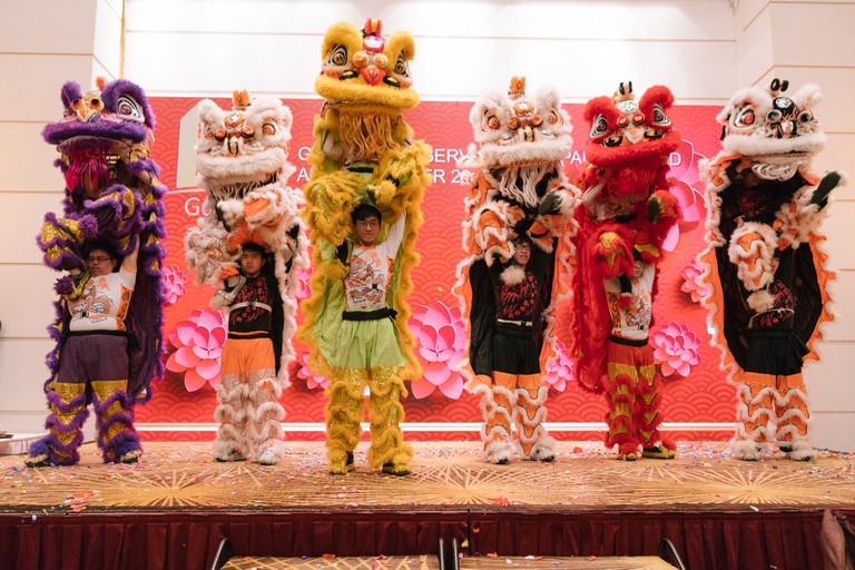 Lion dance performers stand on stage