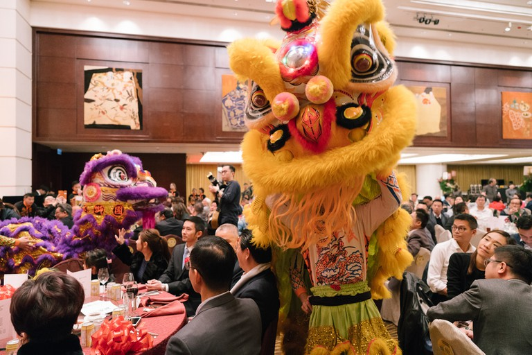 Lion dancers make their way through crowds of people