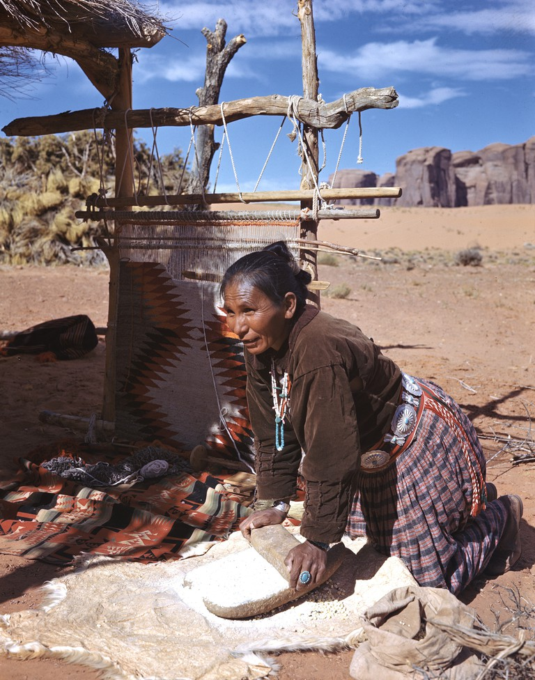 Happy Cly grinding corn. At a summer shelter in Monument Valley on the Navajo Indian Reservation, an Indian woman shows how corn from her own little patch is still ground on the age-old metate. Arizona. (Photographer's caption)