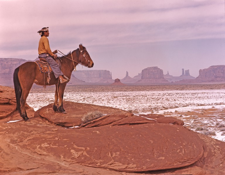 A touch of winter in Monument Valley, Arizona. The colorful Navajo American on his shaggy pony is part of the spectacular desertscape that erupts in great red rock formations, his tribal home for hundreds of years. (photographer's caption)