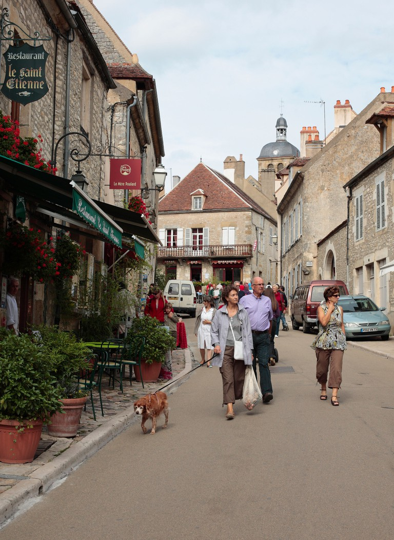 Woman walking a dog in Vezelay, Burgundy, France.