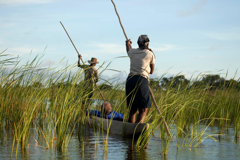 Poler with tourists on their traditional mokoro boat in the Okavango Delta, Botswana, Africa.