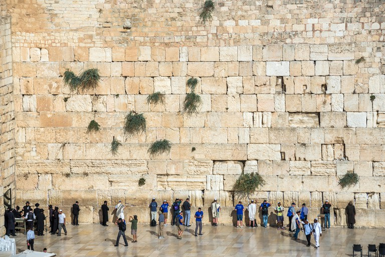 Crowds of people praying at Western Wall in Jewish Quarter of Old Town of Jerusalem, Israel.