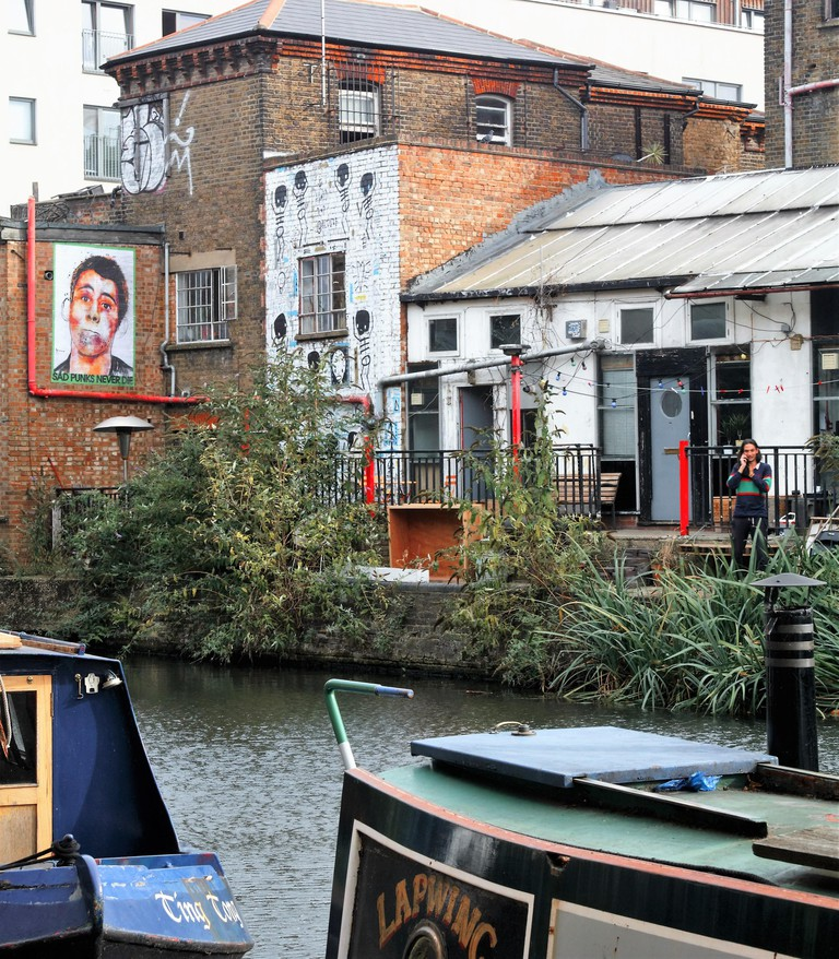 Regents canal near Kingsland Road in Hackney with wall painting of a punk and canal boats in the foreground