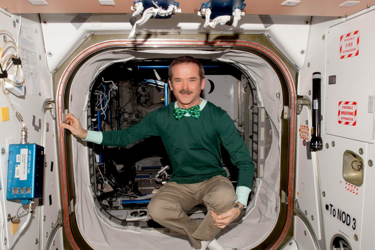 Astronaut Chris Hadfield poses for a photo in the Unity Node 1. He is wearing a green shirt and bow tie in honour of St. Patrick's Day