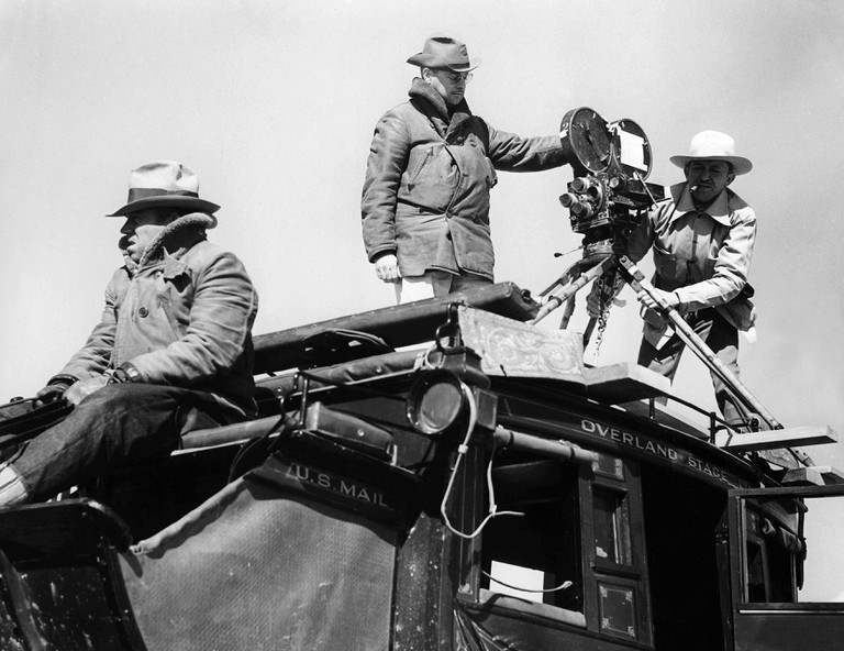 John Ford, seen on the left of the frame directing Stagecoach - 1939. Monument Valley, USA.