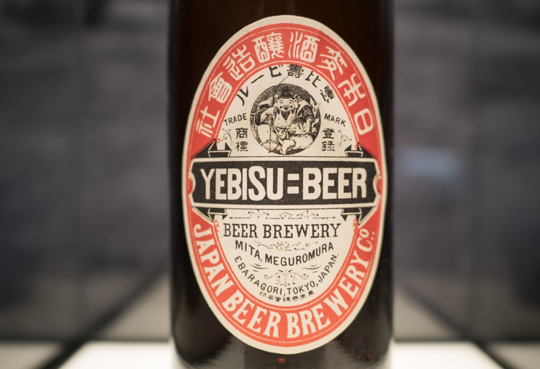 Old beer paper label with two color graphic yebisu logo, red and black, attached on dark brown bottle, demonstrated at Museum of Yebisu Beer exhibition.