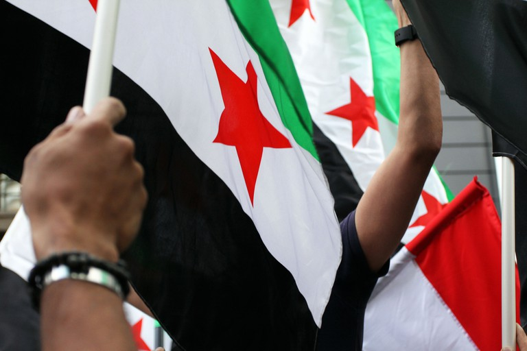 Waving hand Syrian flags