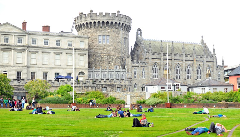 People relax in the Dubh Linn gardens by Dublin Castle in Ireland.