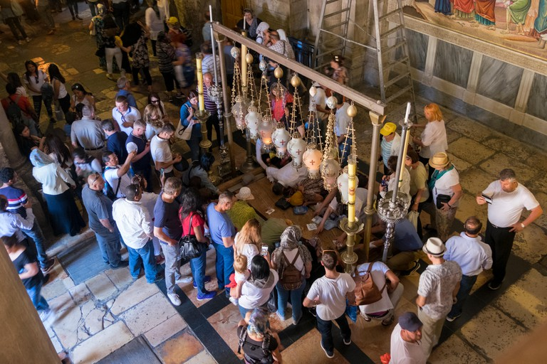 A crowd of penitents gathers around the Stone of Annointing in the Church of the Holy Sepulchre in the Old City of Jerusalem