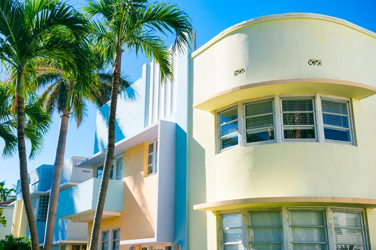 Pastel-colorfed 1930s Art Deco architecture with palm trees in Miami, Florida.