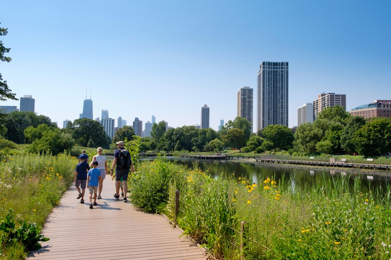 Skyline and family on The Nature Boardwalk at Lincoln Park Zoo in summer, Chicago.