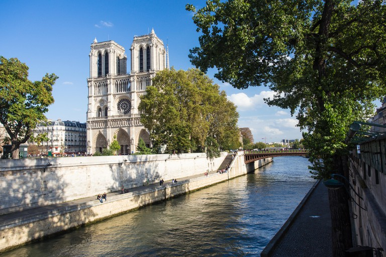 View of Notre Dame Cathedral in Paris France along Seine River