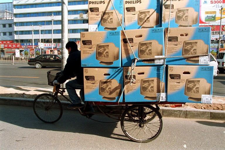 A tricycle rider delivers computer monitors