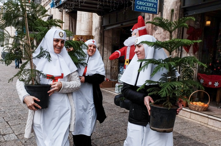 Nuns pick up Christmas trees near Jerusalem's Old City Jaffa Gate
