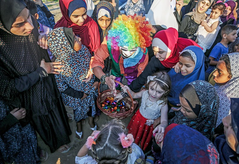 A Palestinian clown distributes sweets to children during Eid Al- Fitr prayers