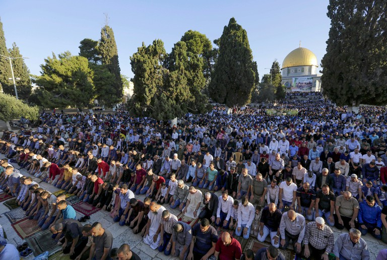Palestinians pray in front of the Dome of the Rock shrine in Jerusalem, during the traditional morning prayer of the Muslim holiday of Eid al-Fitr
