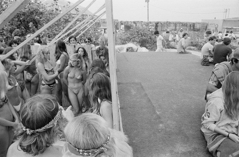 """""""There's one photograph from the first year that got me thinking about the idea and sent me back again. It's a photograph of a bikini contest; there's a group of young women in bikinis on left, and on right there's an empty stage. That photo I always felt was symbolic of the way women are treated. All the events were, if it was about women it was how women looked, and if it was about men it was what they were able to do. There was that dividing line between the two sexes, about how they behaved, and what they were expected to do and perform."""" –Keith McManus"""