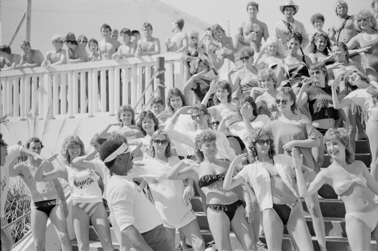 Spring breakers dance in unison to the instructions of a hotel event coordinator